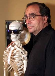"""R.L. Stine, author of the """"Goosebumps"""" childrens books series, poses with his model skeleton sporting sunglasses at his New York apartment Friday, Aug. 25, 2000. The 87 volumes of his series, also adapted into a television show, made his name synonymous with scare among pre-teen readers. (AP Photo/Ed Bailey)"""