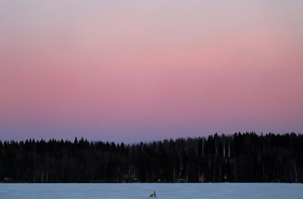 یک زن در حال عبور با کالسکه از روی دریاچه یخ زده لاهتی، فنلاند